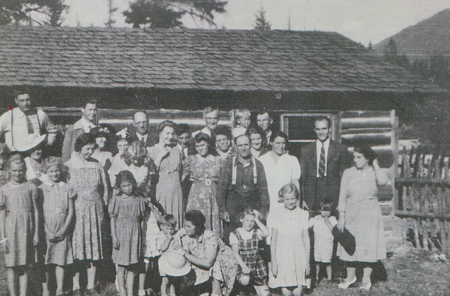 members in front of a log cabin